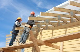 Workers build the new wooden house in Leningrad region. Two floors private construction.
