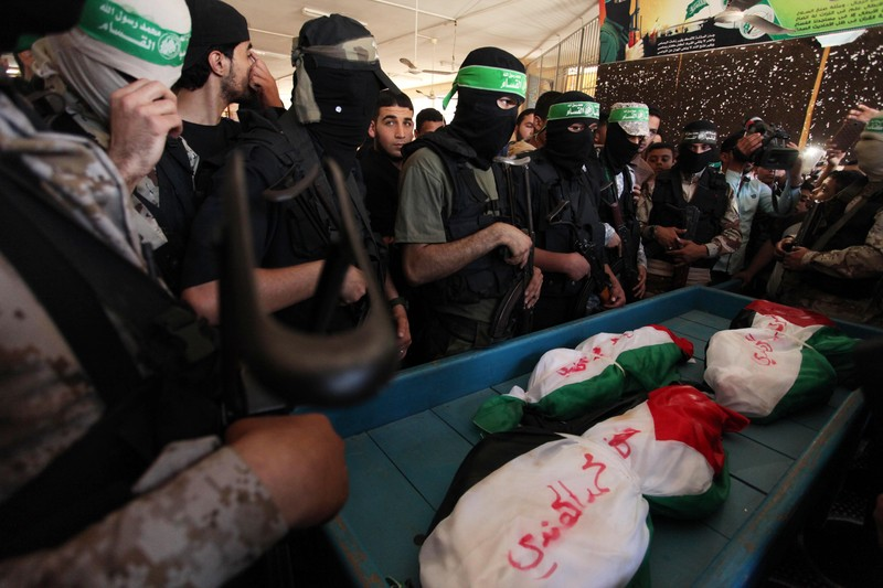 Members of the Ezzedine al-Qassam Brigades, the military wing of the Palestinian Islamist movement Hamas, mourn next to the bodies of three children from the al-Hindi family, who died in a fire caused by a candle at the family home, during their funeral at the al-Shati refugee camp in Gaza City on May 7, 2016. Photo by Ashraf Amra