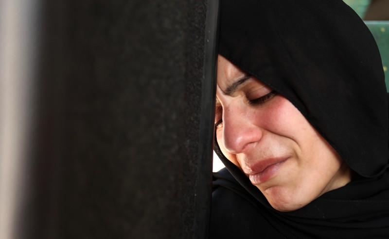 The mother of the al-Hindi family mourns during the funeral of three of her sons who died in a fire caused by a candle at the family home, at the al-Shati refugee camp in Gaza City on May 7, 2016. Photo by Ashraf Amra